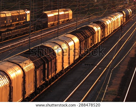 switch yard with trains, wagons, cargo at sunset - stock photo