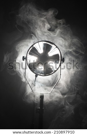 Switched cinema spotlight standing in the dark enveloped in smoke - stock photo
