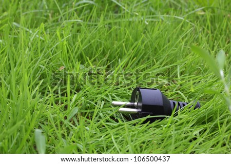 switchplug lying on the grass, energy concept