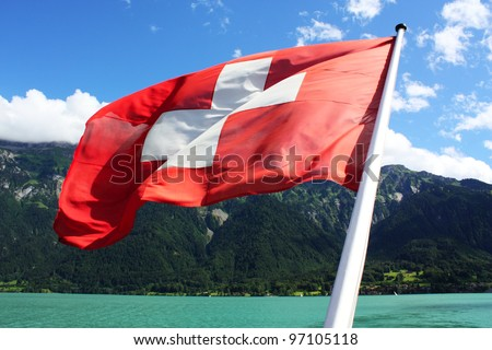 Switzerland flag with lake and mountain in the background - stock photo