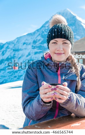 Switzerland's ski resort with a hot drink in their hands