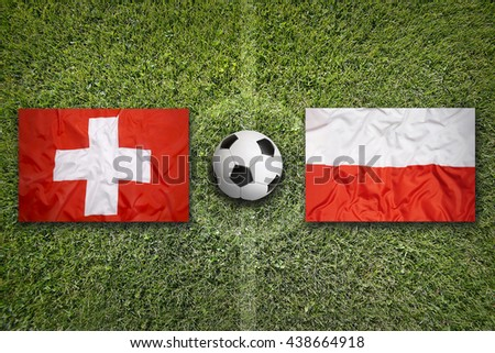 Switzerland vs. Poland flags on green soccer field - stock photo