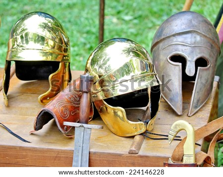 sword and helmets of ancient Roman origin and medieval helmets of brave knights and soldiers - stock photo