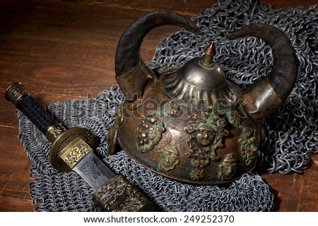 sword, chain armor and the soldier's helmet with horns on a wooden background with beautiful light - stock photo