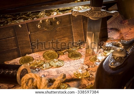 sword, gold coins, monocle, treasure chest and diamonds on a map - stock photo