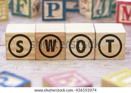 SWOT word written on wood cube - stock photo