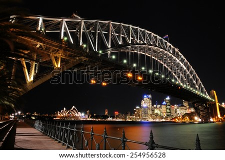 SYDNEY - August 19: The lights of the Sydney Opera House and the downtown Sydney skyline shine under the Sydney Harbour Bridge at night on August 19, 2010 in Sydney, New South Wales, Australia. - stock photo