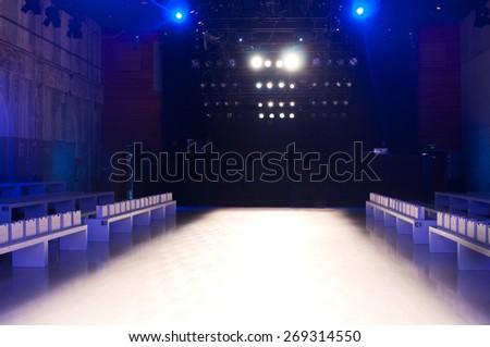 SYDNEY AUSTRALIA - APRIL 14: Empty runway stage behind the scene before start of  Lee Matthews backstage fashion show at Mercedes Benz Fashion Week in Carriageworks Sydney Australia. Focus on seats April 14, 2015 Sydney Australia. - stock photo