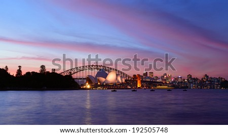 SYDNEY, AUSTRALIA - APRIL 8, 2014: Sunset over Sydney Harbour with Sydney Opera House and Sydney Harbour Bridge in view.
