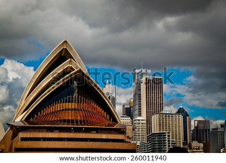 Sydney, Australia - 19 April 2010 : view of the Sydney Opera House from the ferry, against a blue sky with some clouds - stock photo