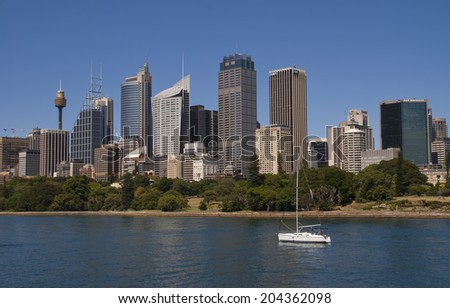 SYDNEY, AUSTRALIA - CIRCA DECEMBER 2009: View from over the bay onto downtown skyline with a lone white yacht in the foreground.