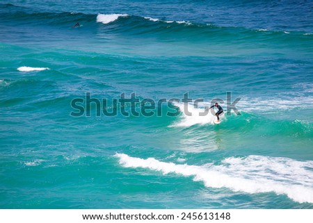 SYDNEY, AUSTRALIA - DEC 10: An unidentified surfer tackles sudden high waves of the Tasman Sea on Bondi Beach in Sydney, Australia on December 10, 2011  - stock photo