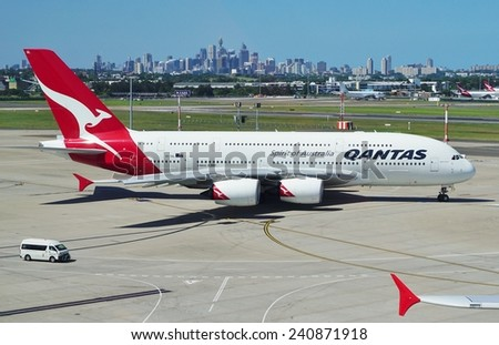 SYDNEY, AUSTRALIA --DECEMBER 2014-- An Airbus A380 jumbo jet airplane from Qantas Airways (QF) gets ready for takeoff at the Kingsford Smith airport (SYD), with the Sydney skyline in the background. - stock photo