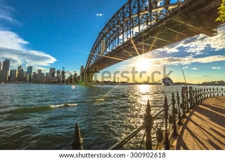 Sydney, Australia - December 29, 2014:Walking on the path that leads beneath the Sydney Harbour Bridge. City skyline, Cruise and australian flag behind at sunset. - stock photo