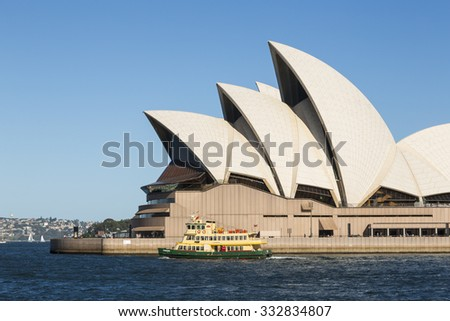 SYDNEY, AUSTRALIA - FEBRUARY 03, 2014: Small Sydney ferry passes Opera House, The Opera House opened in October 1973 and was designed by Jorn Utzon.