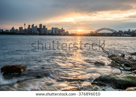 SYDNEY, AUSTRALIA - JAN 23, 2016: The view of Sydney City with Opera house and Harbour bridge in a light sunset. The view of water, wood and rock in the foreground.