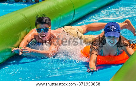"SYDNEY,AUSTRALIA - JANUARY 15,2016: A couple enjoying the ""Slide the city"" event in Centennial Park. Thousands of people paid to travel down a 300-metre water slide on inflatables."