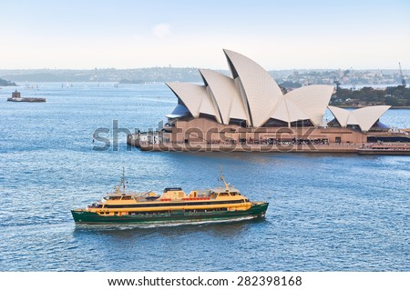 Sydney, Australia - January 23: A ferry passing by Sydney Opera House on January 23, 2015 in Sydney, Australia. The Sydney Opera House is one of the most famous performing arts centers in the world. - stock photo