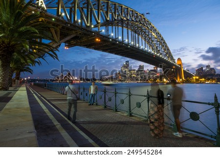 SYDNEY, AUSTRALIA- JANUARY 5, 2015: People taking pictures of the iconic Sydney Harbour Bridge with Sydney Opera House in the background at dusk on a January evening, 2015 - stock photo