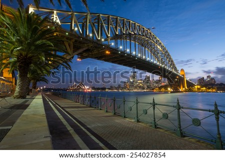 SYDNEY, AUSTRALIA- JANUARY 5, 2015: The iconic Sydney Harbour Bridge with Sydney Opera House in the background at dusk on a January evening, 2015. - stock photo