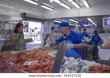 Sydney, Australia-March 17th 2013: A customer buys prawns at Sydney Fish Market. Established in 1945, the market is the world's thied largest. - stock photo