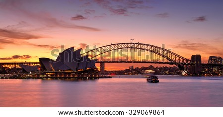 SYDNEY, AUSTRALIA - MAY 25, 2015; Stunning sunset over Sydney Harbour with vibrant reflections in the waters Sydney Harbour Bridge and  Sydney Opera House also in view..  Boats are in motion. - stock photo