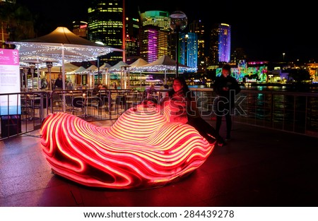 SYDNEY, AUSTRALIA - MAY 27, 2015;   The Heart of the City - A member of the public takes a seat and sensors detect a heart rhythm and the object illuminates with each heart beat - stock photo