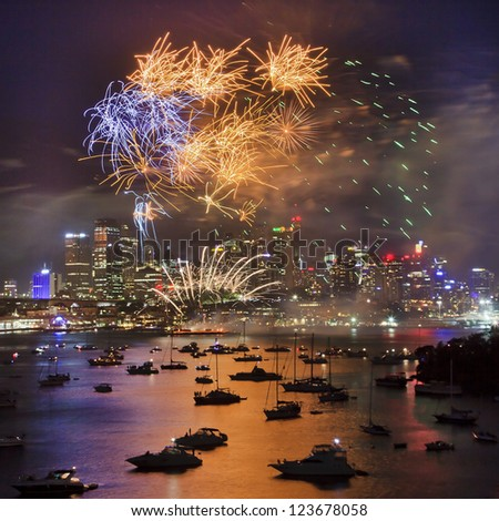 sydney australia new year firework over city cbd and harbour with reflection of lights in water with yachts and illumination - stock photo