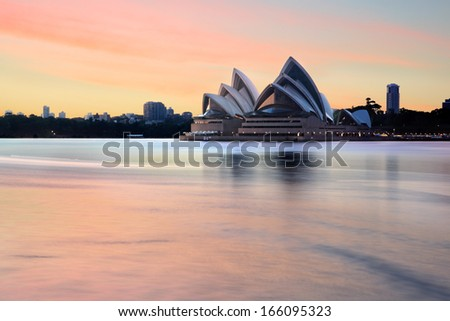 SYDNEY, AUSTRALIA - NOVEMBER 28, 2013; Iconic landmark, the Sydney Opera House and Sydney Harbour and foreshore at sunrise, before most harbour traffic stirs the waters.  Long exposure.