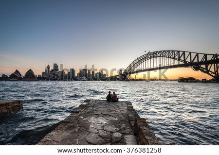 SYDNEY, AUSTRALIA - NOVEMBER 25, 2015: The view of Sydney City with Opera house and Harbour bridge in a light sunset. The people enjoy the views in the foreground.