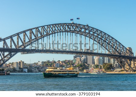 SYDNEY, AUSTRALIA - NOVEMBER 8, 2014: View of the world famous Sydney (Australia) Harbor Bridge, Freshwater ferry sailing past and group of people doing bridge climb. Luna Park in the background.