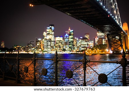 SYDNEY, AUSTRALIA - OCTOBER 21, 2013 Focus at a fence and Bokeh Sydney CBD view from under Harbour Bridge at night on October 21, 2013 in Sydney, Australia