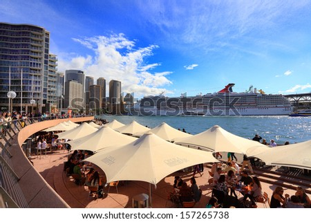 SYDNEY, AUSTRALIA - September 15, 2013:  Carnival Spirit Cruise Liner docked at Circular Quay Sydney.  People at leisure around the harbour, Wispy clouds in the sky.  Winter afternoon. - stock photo
