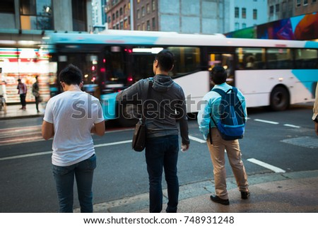 SYDNEY, AUSTRALIA - SEPTEMBER 27, 2017: People waiting to cross the street and bus just passing in front of them.