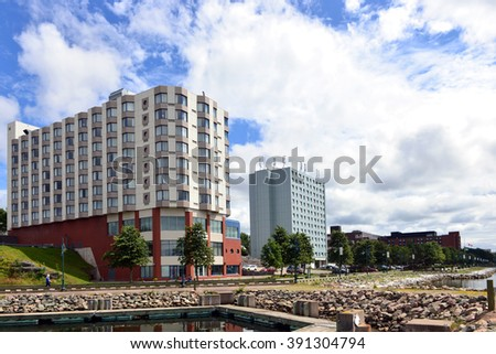 SYDNEY, CANADA - AUG 8, 2015: The waterfront of Sydney on Cape Breton Island in Nova Scotia , including the Holiday Inn, left, and the boardwalk on Sydney Harbour. - stock photo