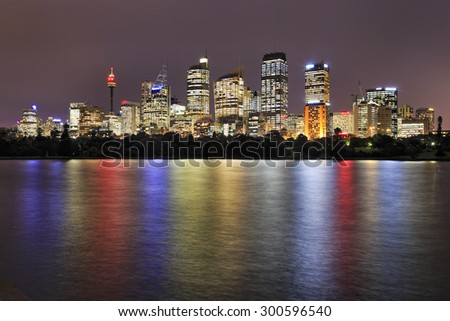 Sydney CBD cityline at sunset from Royal Botanic Garden with bright lights reflection in still blurred waters of Sydney Harbour - stock photo