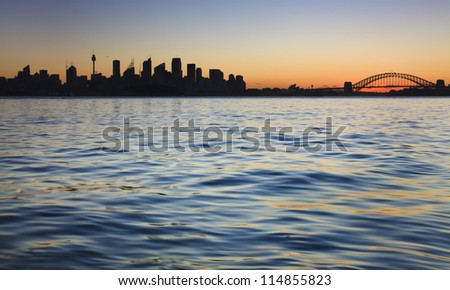 sydney city australia panoramic silhouette view on CBD and harbour bridge with harbour water at sunset