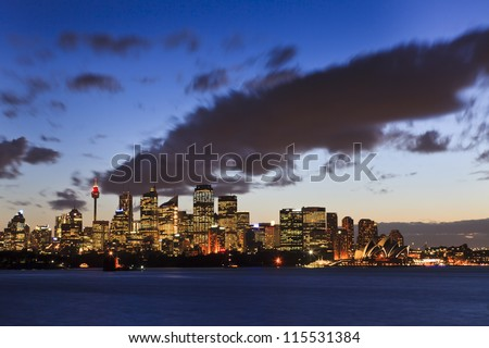 sydney city CBD at sunset under heavy cloud blurred from Cremorne point over harbour water with illuminated lights - stock photo