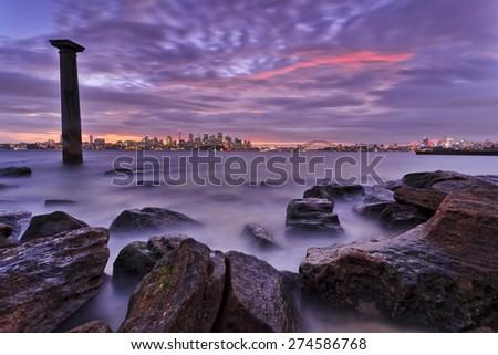Sydney city CBD landmarks distant view from Bradley's head national park at sunset when the city is illuminated and wet tidal rocks on foreground - stock photo