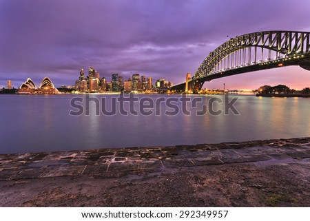 Sydney city CBD landmarks illuminated at sunset and viewed across harbour from Milsons Point. Sydney harbour bridge, skyscrapers and houses