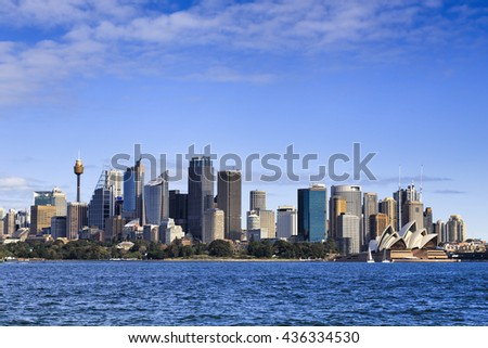 Sydney city CBD towers and office buildings above Royal botanic garden across Harbour waters on a sunny day.