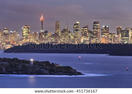 Sydney city CBD towers and office skyscrapers seen from long distance of North Head  entrance to Sydney harbour. South head lighthouse navigating at sunset.