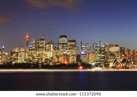 Sydney city cbd view at sunset over harbour with reflection of light illuminated skyscrapers towers and landmark buildings - stock photo
