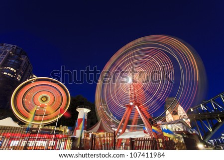 Sydney city luna park illuminated at sunset with blurred moving attractions wheels - stock photo