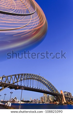 Sydney city luna park segment of spinning illuminated wheel and arch of harbour bridge main attractions of city and australia