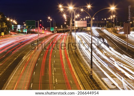 Sydney city motorway at sunset with blurred long exposure traffic vehicles lights and motion rush hour - stock photo