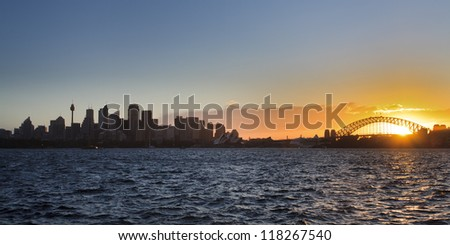 sydney city panoramic view at sunset CBD bridge harbour and opera house over harbour water - stock photo