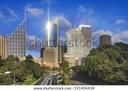 Sydney city skyscraper above multi lane motorway surrounded by trees of botanic garden on sunny summer day - stock photo