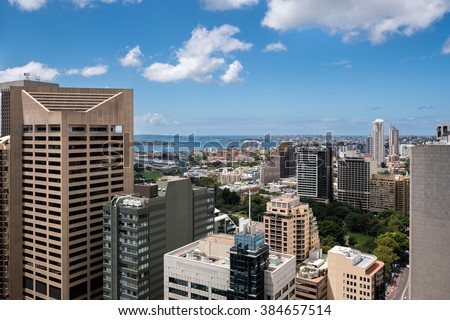 Sydney city with lots of houses and skyscrapers and with few tall buildings as main subject and distant sea - stock photo