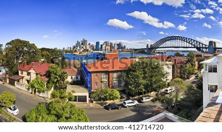 Sydney cityline cityscape from Kirribilli residential suburbs across Sydney Harbour with Bridge arch and CBD sky scrapers in a background. - stock photo